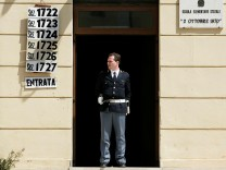 FILE PHOTO: An Italian policeman stands guard in front of a polling station in a school during Italy's general election in Rome