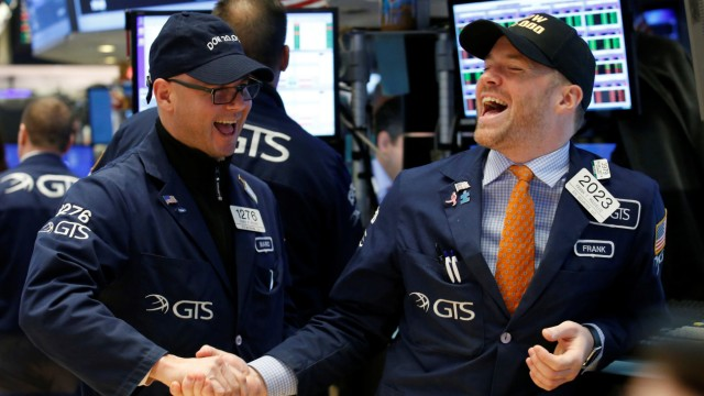 Traders celebrate on the main trading floor of the NYSE as the Dow Jones Industrial Average passes 20,000 after opening of trading session in New York