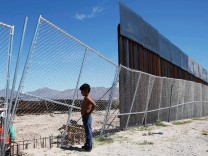 File photo of a boy looking at U.S. workers building a section of the U.S.-Mexico border wall at Sunland Park