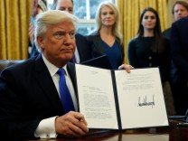 Donald Trump zeigt eines der Dekrete, die er unterzeichnet hat