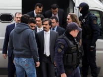 The eight Turkish soldiers, who fled to Greece in a helicopter and requested political asylum after a failed military coup against the government, are escorted by police officers as they arrive at the Supreme Court in Athens