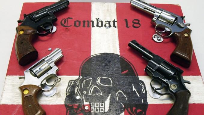 Bei einer Großrazzia sichergestellte Waffen und ein Schild der kriminellen Neonazi-Gruppe