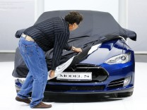File photo of an employee covering a Tesla Model S car during the media day at the Frankfurt Motor Show in Frankfurt