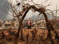 A woman walks amongst burnt houses in Santa Olga