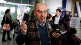 Fuad Sharef Suleman shows his passport to the media after U.S. President Donald Trump's decision to temporarily bar travellers from seven countries, including Iraq, at Erbil International Airport, Iraq