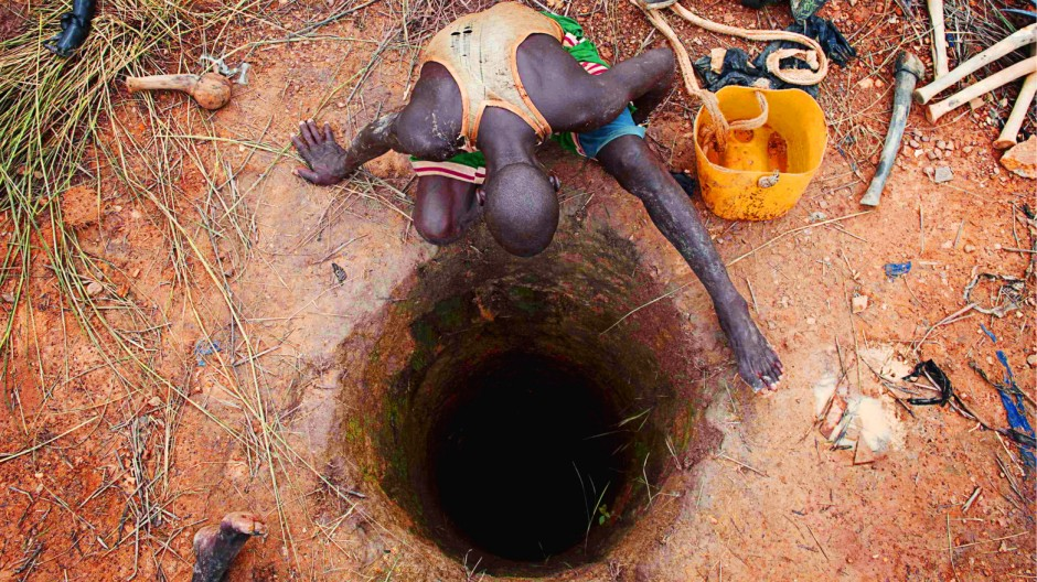 An artisanal gold miner peers into a small-scale mine where his colleague is working in Kalana