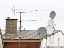 Satellitenschüsseln auf Hausdächern