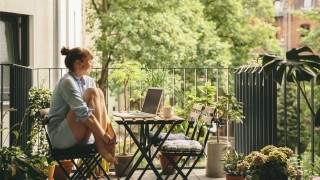 Smiling woman looking at her laptop on balcony model released Symbolfoto property released PUBLICATI