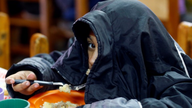 A child eats at the community youth center 'Che Pibe' in Villa Fiorito, on the outskirts of Buenos Aires, Argentina