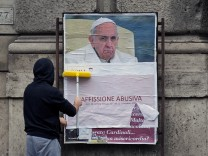 A worker covers with a banner reading 'illegal poster' a poster depicting Pope Francis and accusing him of attacking conservative Catholics is seen in Rome