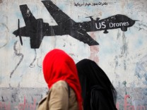 Women walk past a graffiti, denouncing strikes by U.S. drones in Yemen, painted on a wall in Sanaa, Yemen