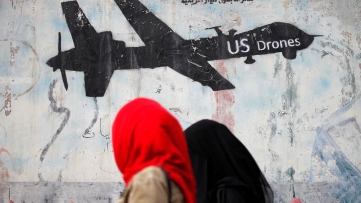 Women walk past a graffiti, denouncing strikes by U.S. drones in Yemen, painted on a wall in Sanaa, Yemen