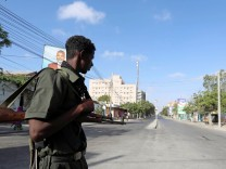 A Somali policeman stands guard along a road which was blocked to control motor vehicle traffic, during a security lock down in Mogadishu