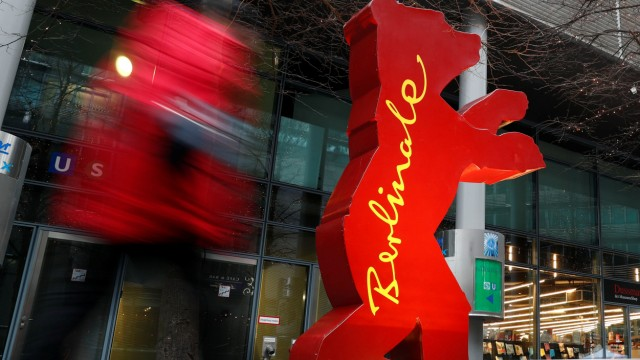 A pedestrian walks by a Berlinale bear advertising for the upcoming 67th Berlin International Film Festival Berlinale in Berlin