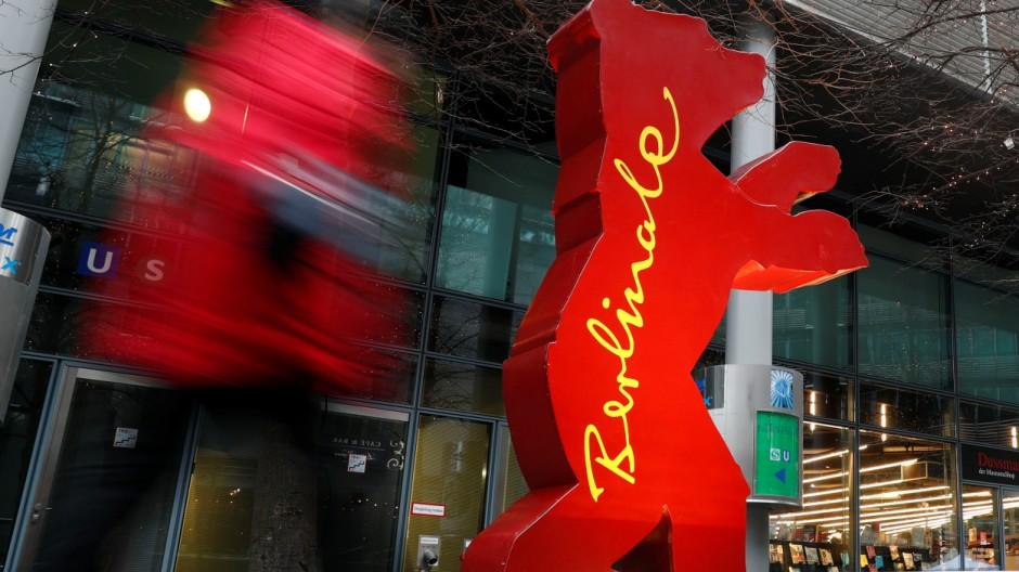 A pedestrian walks by a Berlinale bear advertising for the upcoming 67th Berlin International Film Festival Berlinale in Berlin