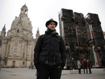 Syrian artist Manaf Halbouni stands next to his art instalation 'Monument' made from three passenger busses near to the 'Frauenkirche' church in Dresden
