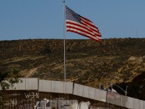 A U.S. flag is seen next to a section of the wall separating Mexico and the United States, in Tijuana