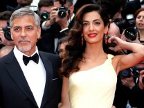 FILE PHOTO - George Clooney and his wife Amal pose on the red carpet as they arrive during the 69th Cannes Film Festival in Cannes