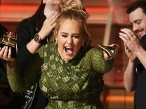 Adele breaks the Grammy for Record of the Year for 'Hello' after having it presented to her at the 59th Annual Grammy Awards in Los Angeles