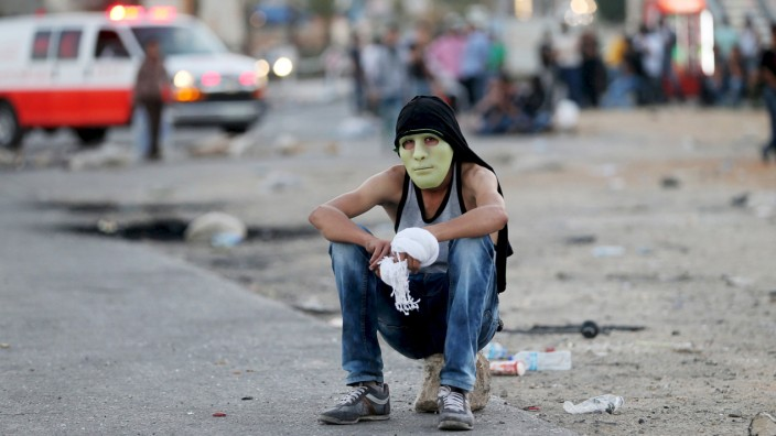 Palestinian protester rests during clashes with the Israeli troops near the Jewish settlement of Bet El, near the West Bank city of Ramallah