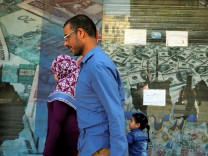 People walk past a closed exchange bureau with an advertisement showing images of the U.S dollar and other foreign currency in Cairo