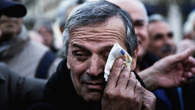 FILE PHOTO:Greek pensioner wipes his face with a fake euro banknote during a demonstration against government policies affecting pensioners in Athens