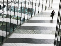 A man is reflected on the glass facade of the Bonn Post Tower in Bonn