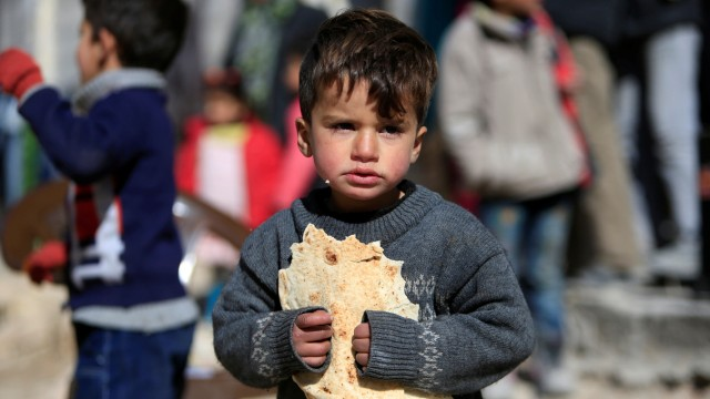 A displaced boy carries bread at a shelter in Jibreen