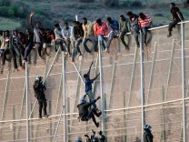An African migrant is pulled from a border fence between Morocco and Melilla by a Spanish civil guard
