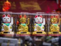 Maneki Neko beckoning cat a common Japanese figurine lucky charm talisman in London UK on Ma