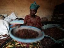 FILE PHOTO:  A woman winnows cocoa beans in Sankadiokrou