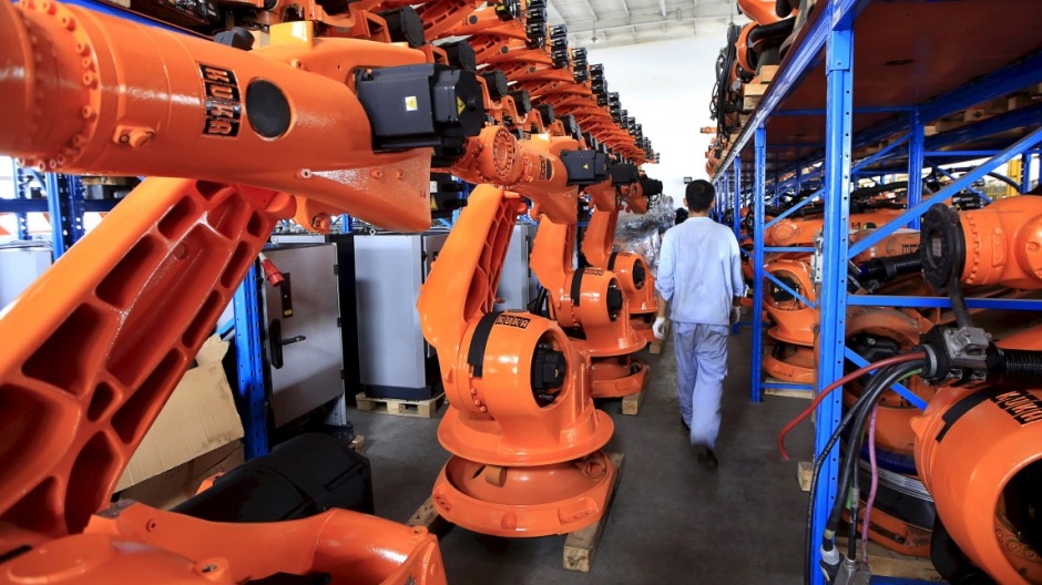 File picture of a worker walking past second-hand robots in a factory in Shanghai
