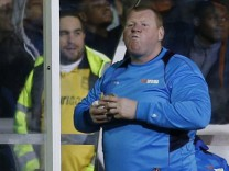 Sutton United's substitute Wayne Shaw eats a pie during the match