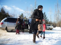 A family that claimed to be from Sudan leaves a taxi to walk across the U.S.-Canada border into Hemmingford, Canada, from Champlain in New York, U.S.