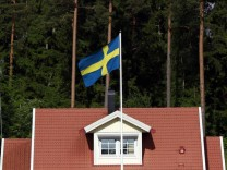 The Swedish national flag flies in front of a house near the town of Sodertalje, south west of Stockholm