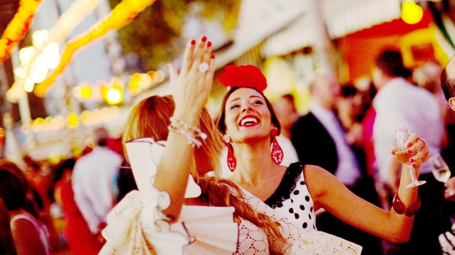 Women wearing Sevillana dresses dance during the traditional Feria de Abril (April fair) in the Andalusian capital of Seville