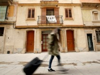 FILE PHOTO - A banner against apartments for tourists hangs from a balcony as a woman pulls a suitcase at Barceloneta neighborhood in Barcelona