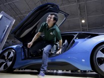 FILE PHOTO:A visitor gets out of a new BMW i8 plug-in hybrid sports car during the Auto China 2016 in Beijing