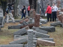 People view toppled Jewish headstones after a weekend vandalism attack on Chesed Shel Emeth Cemetery in University City