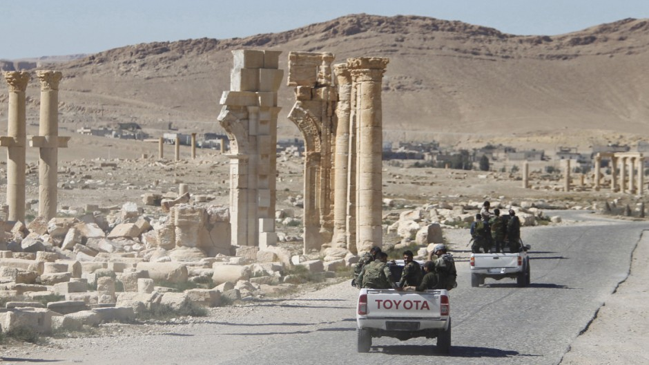 FILE PHOTO: Syrian army soldiers drive past the Arch of Triumph in the historic city of Palmyra, in Homs Governorate