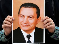 Supporter of former Egyptian President Hosni Mubarak holds up his picture while waiting for him to be transferred to a court, in front of Maadi military hospital in Cairo