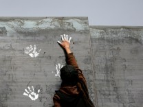 Activist paints the U.S.-Mexico border wall between Ciudad Juarez and New Mexico as a symbol of protest against US President Donald Trump's new immigration reform in Ciudad Juarez, Mexico