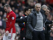 Manchester United's Wayne Rooney walks past manager Jose Mourinho as he is substituted