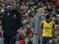 Arsenal's Theo Walcott and Lucas Perez prepare to come on as a substitute as Arsenal manager Arsene Wenger and Liverpool manager Juergen Klopp look on
