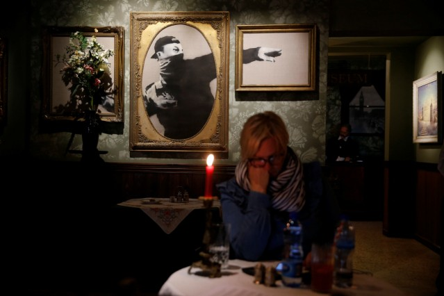 Woman sits in in the Walled Off hotel which was opened by street artist Banksy, in the West Bank city of Bethlehem