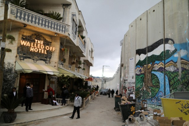 People stand outside the Walled Off hotel, which was opened by street artist Banksy, in the West Bank city of Bethlehem