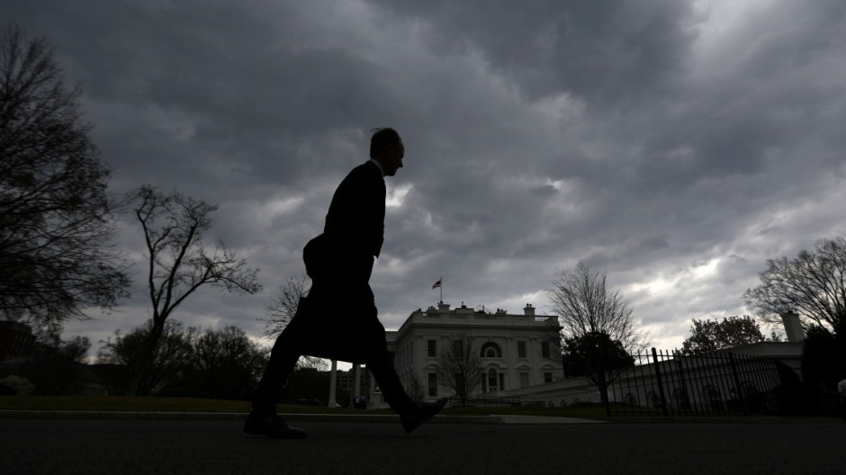 A man walks on the North Lawn of the White House as a thunderstorm approaches the Washington D.C. area