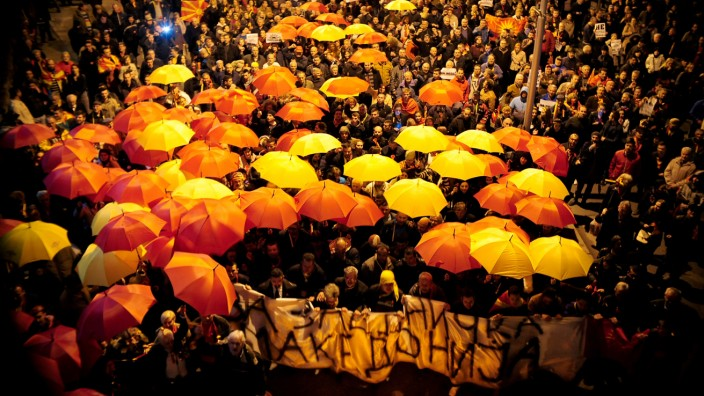 Protesters shout slogans while holding red and yellow umbrellas during demonstrations against an agreement that would ensure the wider official use of the Albanian language, in Skopje, Macedonia