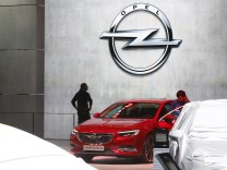 Visitors walk past new Opel Insignia car during the 87th International Motor Show at Palexpo in Geneva