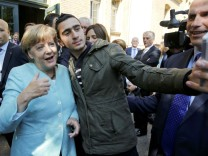 FILE PHOTO: Syrian refugee Modamani takes a selfie with German Chancellor Merkel outside a refugee camp in Berlin